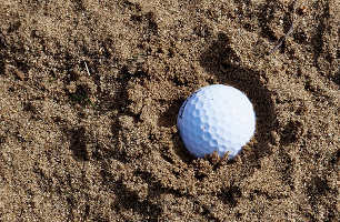 The ball is lying in the sand.