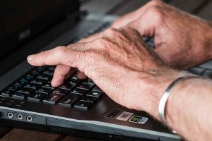 Old hands typing on a laptop